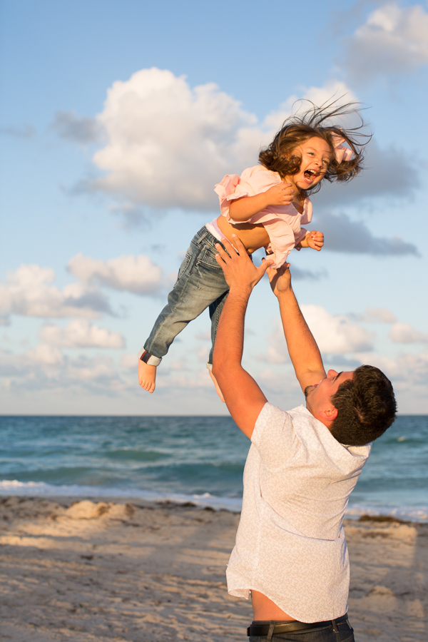 Father throwing daughter in air Miami Beach sunset
