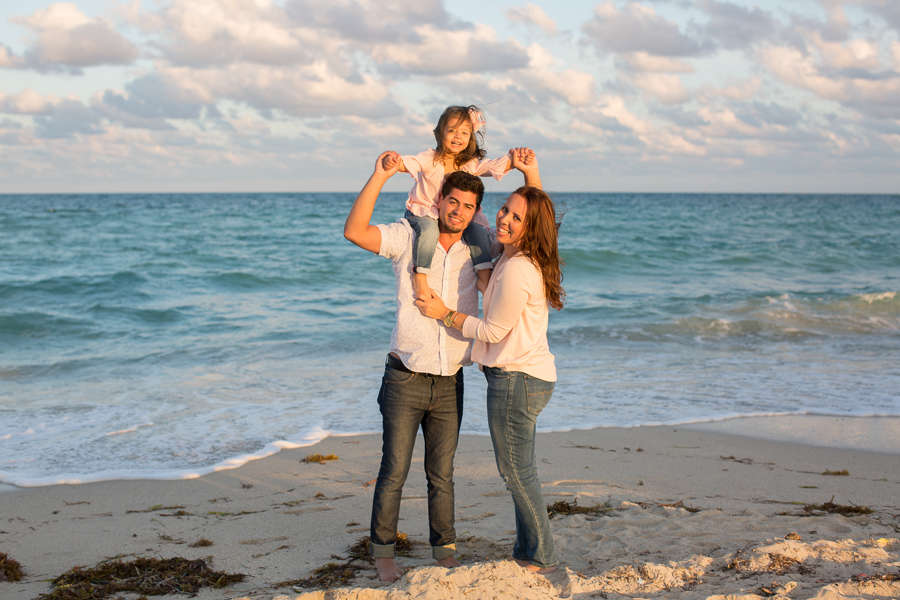 Family of three on Miami Beach at sunset