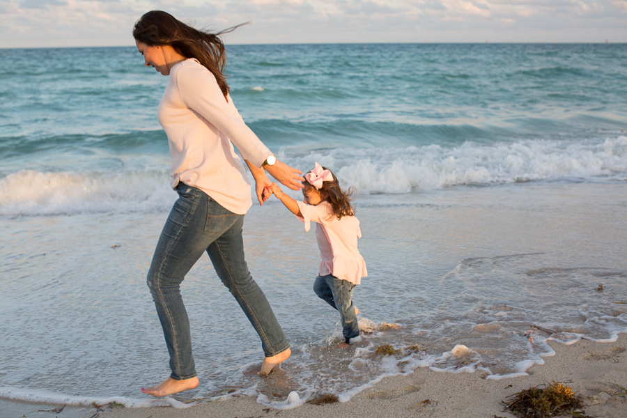 Mother daughter running on ocean Miami Beach