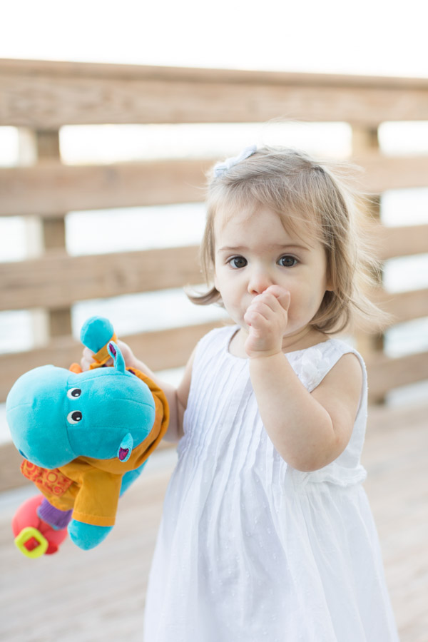 Little girl with thumb in her mouth holding her toy.