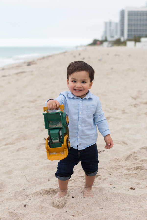 boy playing on beach with truck