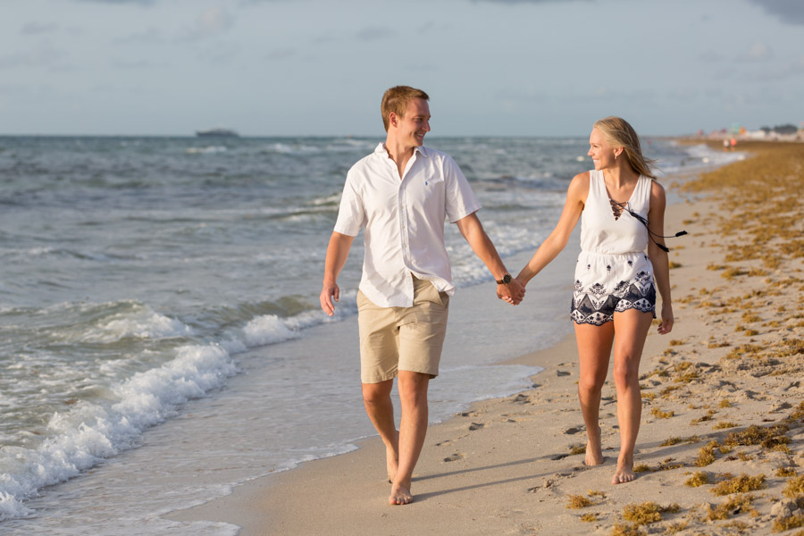 couple holding hands walking on miami beach