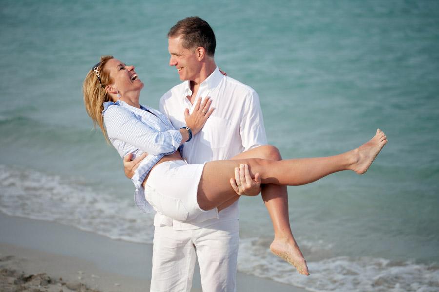 husband picking up wife on beach